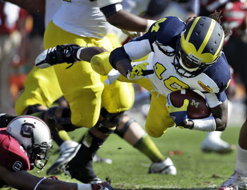 Michigan quarterback Denard Robinson (16) is tripped up by South Carolina linebacker DeVonte Holloman (21) during the first quarter of the Outback Bowl NCAA college football game, Tuesday, Jan. 1, 2013, in Tampa, Fla. (AP Photo/Chris O'Meara)