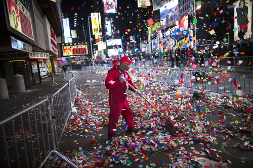 A worker clears confetti from a sidewalk in Times Square after midnight on New Years Tuesday Jan. 1, 2013, in New York. With fireworks, concerts and celebrations from Hong Kong to New York, revelers welcome 2013 with hope for a better future after a year that thudded to a close with a disastrous storm, gun violence, and talk of economic turmoil from a looming fiscal cliff. This will be the first Times Square countdown in decades without Dick Clark, who died in April, and will be honored with a tribute concert and his name printed on pieces of confetti. (AP Photo/John Minchillo)