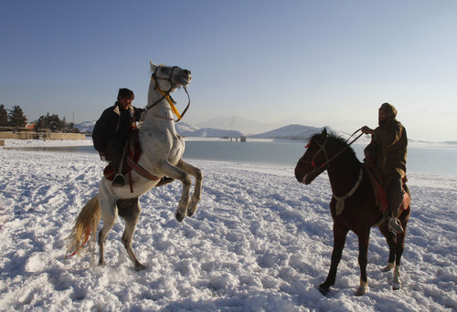 Afghan men ride horses in the snow on the shores of Lake Qargha in Kabul, Afghanistan, Tuesday, Jan, 1, 2013. (AP Photo/Ahmad Jamshid)