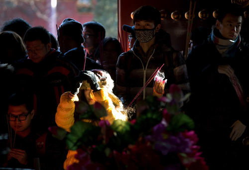 A Chinese woman holds incense in the air as she is struck by a beam of sunlight while offering prayers with others on the first day of the New Year at the Yonghegong Lama Temple in Beijing Tuesday, Jan. 1, 2013. (AP Photo/Andy Wong)