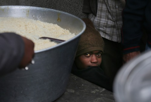 A homeless person waits under a table for free food in New Delhi, India, Tuesday, Jan. 1, 2013. There are over 300,000 homeless people in New Delhi, living on the streets, braving extreme weather and economic hardship, according to news reports. (AP Photo/ Manish Swarup)