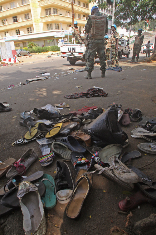 U.N. troops stand near the shoes  of people that were involved in a stampede in Abidjan, Ivory Coast, Tuesday. Jan, 1, 2013. At least 61 people were killed early Tuesday in a stampede following a New Year's fireworks display in Abidjan, Ivory Coast's commercial center, said officials. The death toll is expected to rise, according to rescue workers. The majority of those killed were young people between eight and 15 years old who were trampled after the fireworks festivities in Abidjan's Plateau district, at about 1 a.m. Tuesday, said Col. Issa Sako, of the fire department rescue team. (AP Photo/Emanuel Ekra)
