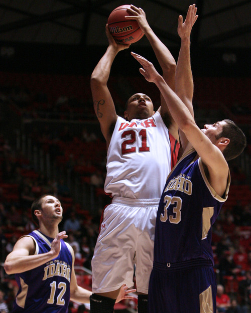 Utah forward Jordan Loveridge (21) shoots against College of Idaho's Taylor Pruett, right, during an NCAA college basketball game in Salt Lake City on Friday, Dec. 28, 2012. Utah defeated College of Idaho 72-38. (AP Photo/The Salt Lake Tribune, Kim Raff)