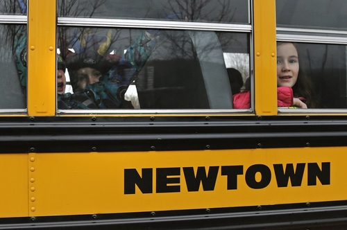 Schoolchildren look out the window of their bus as they head back to school in Newtown, Conn., Tuesday, Dec. 18, 2012. Classes resume Tuesday for Newtown schools except those at Sandy Hook. Buses ferrying students to schools were festooned with large green and white ribbons on the front grills, the colors of Sandy Hook. At Newtown High School, students in sweatshirts and jackets, many wearing headphones, betrayed mixed emotions.  Adam Lanza walked into Sandy Hook Elementary School in Newtown,  Friday and opened fire, killing 26 people, including 20 children, before killing himself. (AP Photo/Charles Krupa)