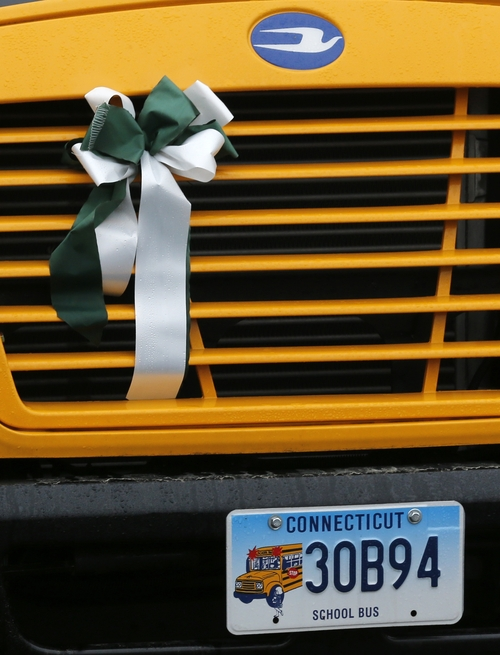 A green and white memorial ribbon is attached to the grill of a school bus as it rolls through town in Newtown, Conn., Tuesday, Dec. 18, 2012. Classes resume Tuesday for Newtown schools except those at Sandy Hook. Buses ferrying students to schools were festooned with large green and white ribbons on the front grills, the colors of Sandy Hook. At Newtown High School, students in sweatshirts and jackets, many wearing headphones, betrayed mixed emotions.  Adam Lanza walked into Sandy Hook Elementary School in Newtown,  Friday and opened fire, killing 26 people, including 20 children, before killing himself.(AP Photo/Jason DeCrow)