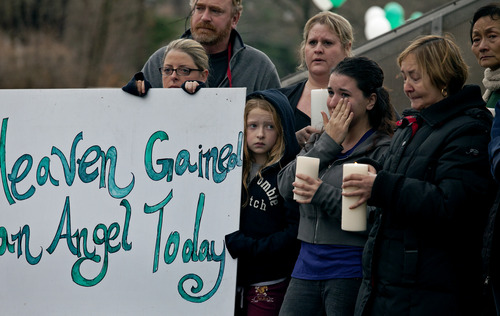 Susan Sheperd wipes a tear as she stands with friends and co-workers  as the funeral procession for James Mattioli, 6, who died in the Sandy Hook Elementary School shootings, approaches the St. John's Cemetery Tuesday, Dec. 18, 2012, in Darien, Conn. Center are his wife Debbie and daughter Emily, 10. Adam Lanza walked into Sandy Hook Elementary School in Newtown Dec. 14, and opened fire, killing 26 people, including 20 children. (AP Photo/Craig Ruttle)