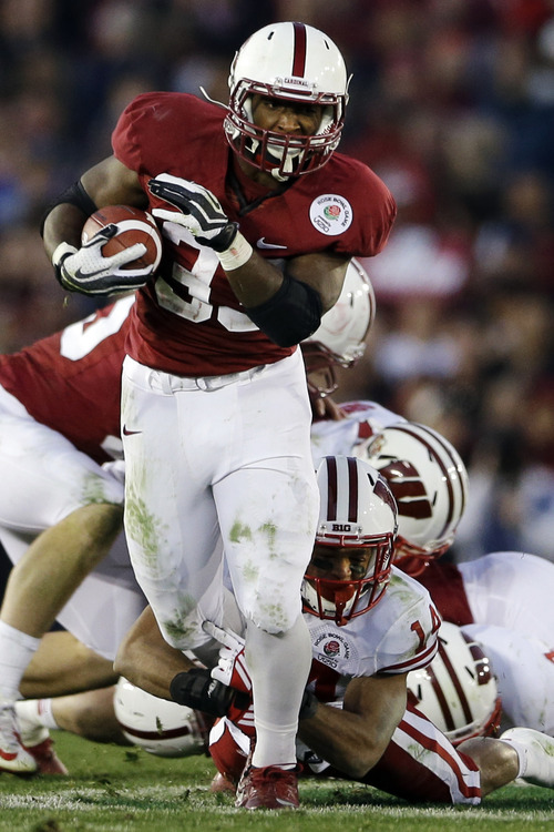Stanford running back Stepfan Taylor breaks through Wisconsin defensive back Nate Hammon (14) during the second half of the Rose Bowl NCAA college football game, Tuesday, Jan. 1, 2013, in Pasadena, Calif. Stanford won 20-14. (AP Photo/Lenny Ignelzi)