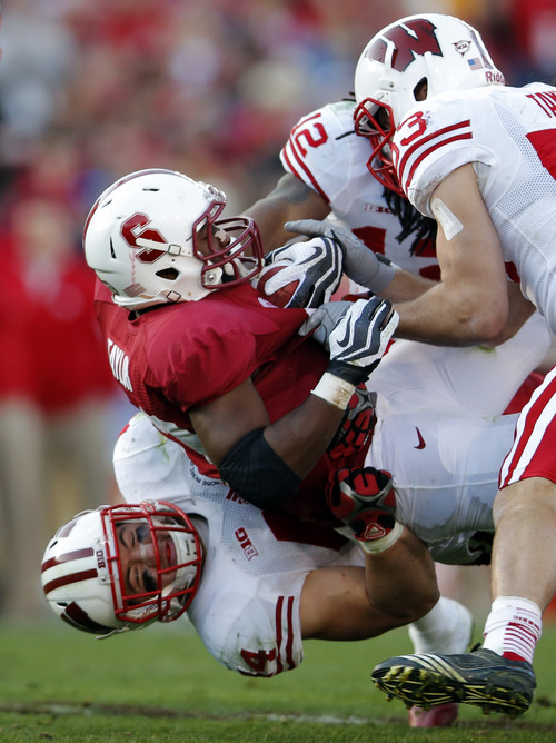 Wisconsin linebacker Chris Borland, bottom, brings down Stanford running back Stepfan Taylor during the second half of the Rose Bowl NCAA college football game, Tuesday, Jan. 1, 2013, in Pasadena, Calif. (AP Photo/Jae C. Hong)