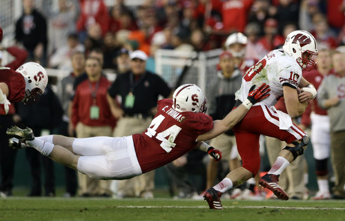 Stanford linebacker Chase Thomas attempts to take down Wisconsin quarterback Curt Phillips during the second half at the Rose Bowl NCAA college football game Tuesday, Jan. 1, 2013, in Pasadena, Calif. (AP Photo/Lenny Ignelzi)