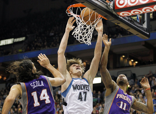 Minnesota Timberwolves forward Andrei Kirilenko (47) scores between Phoenix Suns forwards Luis Scola (14) and Markieff Morris (11) during the first half of an NBA basketball game, Saturday, Dec. 29, 2012, in Minneapolis. (AP Photo/Genevieve Ross)
