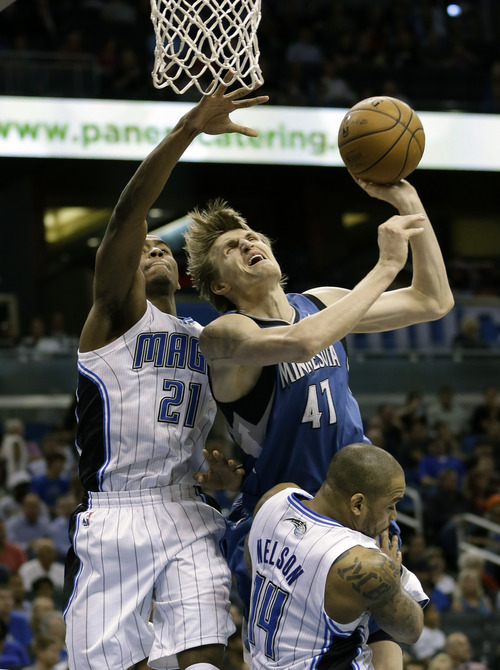 Minnesota Timberwolves' Andrei Kirilenko (47), of Russia, makes a shot as he collides with Orlando Magic small forward Moe Harkless (21) and Jameer Nelson (14) during the first half of an NBA basketball game, Monday Dec.  17, 2012, in Orlando, Fla. (AP Photo/John Raoux)