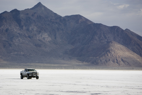 Jim Urquhart | Tribune file photo A truck drives along the Bonneville Salt Flats near Wendover with Pilot Peak in the background.