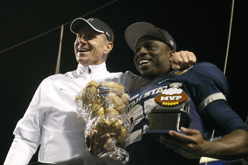 Chris Detrick  |  The Salt Lake Tribune Utah State Aggies head coach Gary Andersen and Utah State Aggies running back Kerwynn Williams (25) pose for pictures with the trophy after winning the Famous Idaho Potato Bowl at Bronco Stadium Saturday December 15, 2012.  The Aggies beat the Rockets, 41-15.