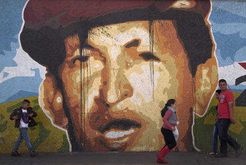 People walk a mural depicting Venezuela's President Hugo Chavez past in Caracas, Venezuela, Thursday, Jan. 3, 2013. The ailing president's health crisis has raised contentious questions ahead of the swearing-in set for Jan. 10, including whether the inauguration could legally be postponed. Officials have raised the possibility that Chavez might not be well enough to take the oath of office, without saying what will happen if he can't. The constitution says that if a president or president-elect dies or is declared unable to continue in office, presidential powers should be held temporarily by the president of the National Assembly and that a new presidential vote should be held within 30 days. (AP Photo/Ariana Cubillos)