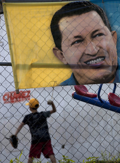 A boy plays behind a poster with an image depicting Venezuela's President Hugo Chavez in Caracas, Venezuela, Thursday, Jan. 3, 2013. The ailing president's health crisis has raised contentious questions ahead of the swearing-in set for Jan. 10, including whether the inauguration could legally be postponed. The ailing president's health crisis has raised contentious questions ahead of the swearing-in set for Jan. 10, including whether the inauguration could legally be postponed. Officials have raised the possibility that Chavez might not be well enough to take the oath of office, without saying what will happen if he can't. The constitution says that if a president or president-elect dies or is declared unable to continue in office, presidential powers should be held temporarily by the president of the National Assembly and that a new presidential vote should be held within 30 days. (AP Photo/Ariana Cubillos)