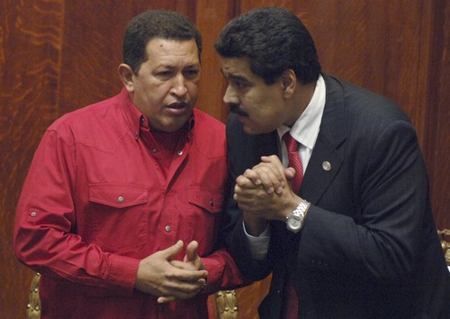 """FILE - In this Dec. 18, 2007 file photo Venezuela's President Hugo Chavez, left, talks to then Foreign Minister Nicolas Maduro at the University of Uruguay in Montevideo, Uruguay.  Chavez hasn't been seen or heard from since his Dec. 11 cancer surgery, and speculation has grown that his illness could be reaching its final stages. Maduro, who is now vice president and Chavez's chosen successor, is reported to have delayed plans to return home Wednesday, Jan. 2, 2013, after at least two bedside visits with Chavez. The government has provided few details but describes the ailing president's condition, after complications due to a respiratory infection, as """"delicate."""" (AP Photo/Matilde Campodonico, File)"""