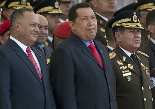 FILE - In this June 24, 2012 file photo, Venezuela's National Assembly President Diosdado Cabello, left, President Hugo Chavez, center, and Defense Minister Gen. Henry Rangel attend a military parade in Caracas, Venezuela. Chavez hasn't been seen or heard from since his Dec. 11 cancer surgery, and speculation has grown that his illness could be reaching its final stages. Cabello, who is thought to wield power within the military and who would be in line to temporarily assume the presidency until a new election can be held. Cabello has dismissed rumors of any discord within the socialist party. (AP Photo/Ariana Cubillos, File)