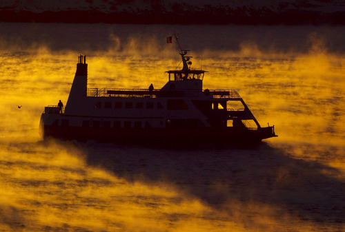 Two passengers brave the frigid weather while riding outside on a ferry crossing Casco Bay in Portland, Maine, at sunrise, Thursday, Jan. 3, 2013. The overnight low temperature dropped to 0 degrees Fahrenheit in Portland. The combination of cold air and warmer ocean water created the arctic sea smoke. (AP Photo/Robert F. Bukaty)