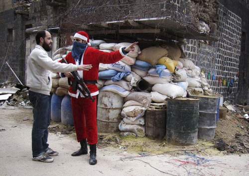 In this picture taken on Tuesday, Jan. 1, 2013, a citizen journalism image provided by Lens Young Homsi, which has been authenticated based on its contents and other AP reporting, a Free Syrian Army fighter wears as a Santa Claus suit and holds his AK-47, right, as he directs a civilian man, in the old city of Homs, Syria. (AP Photo/Lens Young Homsi)