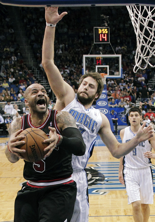 Chicago Bulls forward Carlos Boozer, left, goes to the basket in front of Orlando Magic's Josh McRoberts during the second half of an NBA basketball game, Wednesday, Jan. 2, 2013, in Orlando, Fla. Chicago won 96-94. (AP Photo/John Raoux)