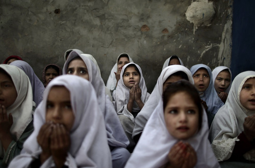 Pakistani schoolgirls, who were displaced with their families from Pakistan's tribal areas due to fighting between militants and the army, chant prayers during a class to pay tribute for five female teachers and two aid workers who were killed by gunmen on Tuesday, at a school in a slum on the outskirts of Islamabad, Pakistan, Thursday, Jan. 3, 2013. Gunmen in northwest Pakistan killed five female teachers and two aid workers on Tuesday in an ambush on a van carrying workers home from their jobs at a community center, officials said. (AP Photo/Muhammed Muheisen)