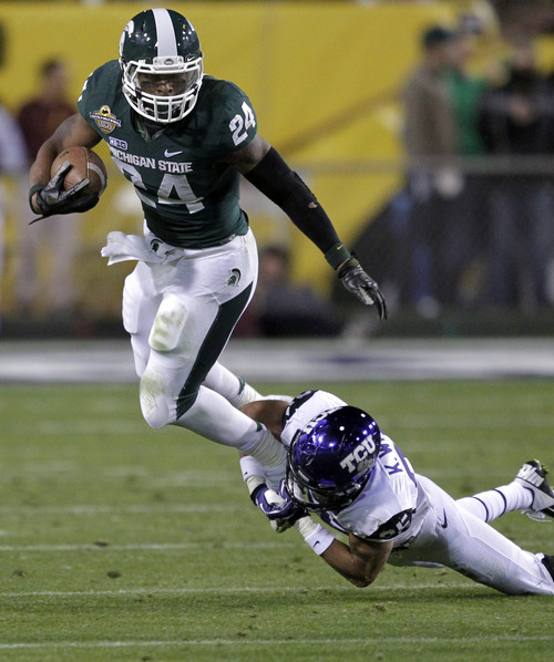 Michigan State running back Le'Veon Bell (24) is tripped up by TCU cornerback Kevin White (25) during the first half of the Buffalo Wild Wings Bowl NCAA college football game, Saturday, Dec. 29, 2012, in Tempe, Ariz. (AP Photo/Matt York)