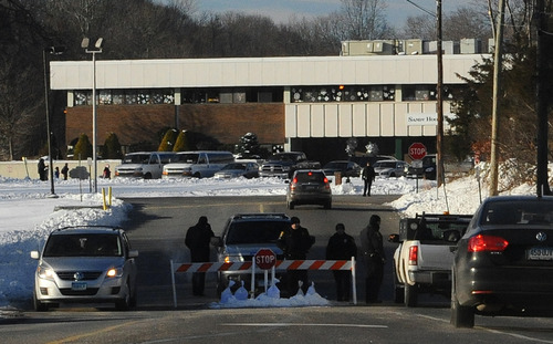 A police road block is at the entrance to the new Sandy Hook Elementary School on the first day of classes in Monroe, Conn., Thursday, Jan. 3, 2013. The school, formerly known as Chalk Hill School, was overhauled specially for the students from the Sandy Hook School shooting in Newtown, in the neighboring town of Monroe, Conn. (AP Photo/Jessica Hill)