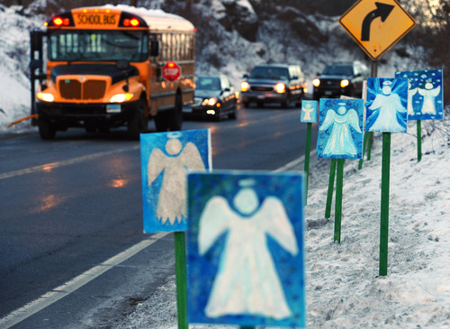 A bus traveling from Newtown, Conn., to Monroe stops in front of 26 angels along the roadside on the first day of classes for Sandy Hook Elementary School students since the Dec. 14 shooting, in Monroe, Conn., Thursday, Jan. 3, 2013. Chalk Hill School in Monroe was overhauled especially for the students from the Sandy Hook School shooting. (AP Photo/Jessica Hill)