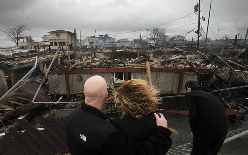 """FILE - In this Tuesday, Oct. 30, 2012, file photo, Robert Connolly, left, embraces his wife Laura as they survey the remains of the home owned by her parents that burned to the ground in the Breezy Point section of New York, during Superstorm Sandy. The current term of the U.S. Congress is set to end this week with no action on aid for the superstorm that left more than 100 dead and thousands homeless in three northeast states. Governors Andrew Cuomo of New York and Chris Christie of New Jersey said in a joint statement Wednesday, Jan. 2, 2013 that the """"continued inaction and indifference"""" by the House """"'is inexcusable."""" (AP Photo/Mark Lennihan, File)"""