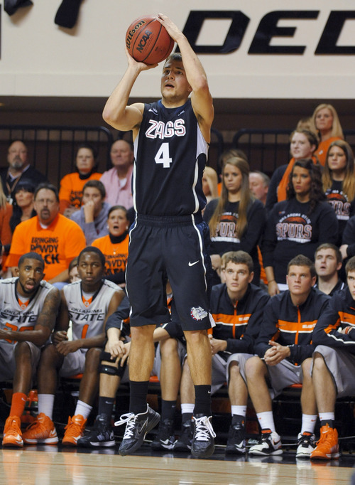 Gonzaga guard Kevin Pangos takes a 3-point shot in front of the Oklahoma State bench during the first half of an NCAA college basketball game in Stillwater, Okla., Monday, Dec. 31, 2012. Pangos led Gonzaga scorers with 23 points in the team's 69-68 win over Oklahoma State. (AP Photo/Brody Schmidt)