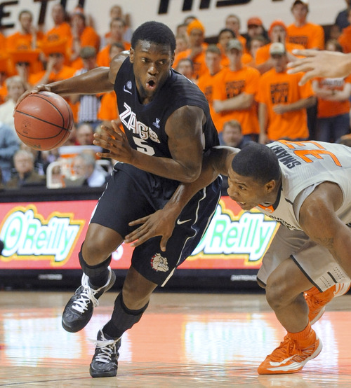 Oklahoma State guard Marcus Smart, right, loses his balance while defending Gonzaga guard Gary Bell Jr. during the first half of an NCAA college basketball game in Stillwater, Okla., Monday, Dec. 31, 2012. Gonzaga won 69-68. (AP Photo/Brody Schmidt)