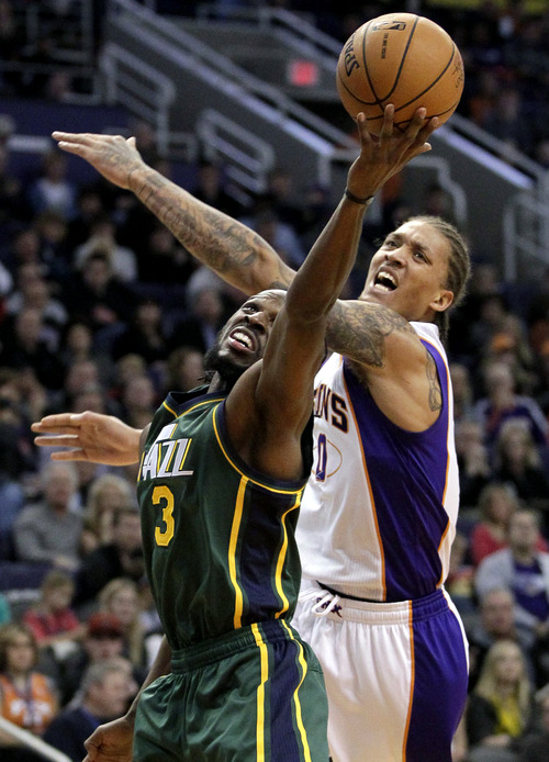 Utah Jazz forward DeMarre Carroll (3) pulls down a rebound over Phoenix Suns forward Michael Beasley (0) during the first half of an NBA basketball game, Friday, Jan. 4, 2013, in Phoenix. (AP Photo/Matt York)