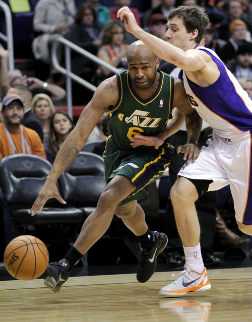 Utah Jazz guard Jamaal Tinsley (6) drives against Phoenix Suns guard Goran Dragic, of Slovenia, during the first half of an NBA basketball game, Friday, Jan. 4, 2013, in Phoenix. (AP Photo/Matt York)