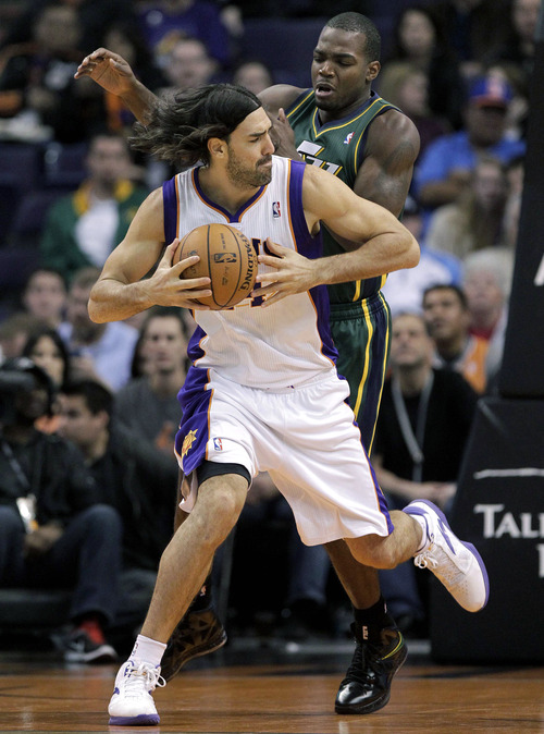 Phoenix Suns forward Luis Scola, of Argentina, backs down Utah Jazz forward Paul Millsap during the first half of an NBA basketball game, Friday, Jan. 4, 2013, in Phoenix. (AP Photo/Matt York)