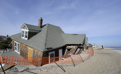 A man photographs a beach front home in Bay Head, N.J., Thursday, Jan. 3, 2013, that was severely damaged two months ago by Superstorm Sandy. New Jersey Gov. Chris Christie, a Republican who has praised President Barack Obama's handling of the devastating storm, has blasted Republican U.S. House Speaker John Boehner for delaying a vote for federal storm relief. Now, under intense pressure from angry Republicans, Boehner has agreed to a vote this week on aid for Superstorm Sandy recovery. (AP Photo/Mel Evans)