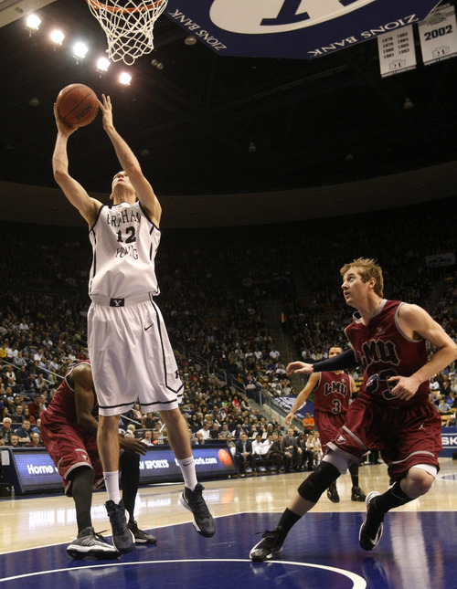 Chris Detrick  |  The Salt Lake Tribune Brigham Young Cougars forward Josh Sharp (12) shoots past Loyola Marymount Lions guard Chase Flint (23) during the first half of the game at  Thursday January 3, 2013.  BYU is winning the game 35-20.