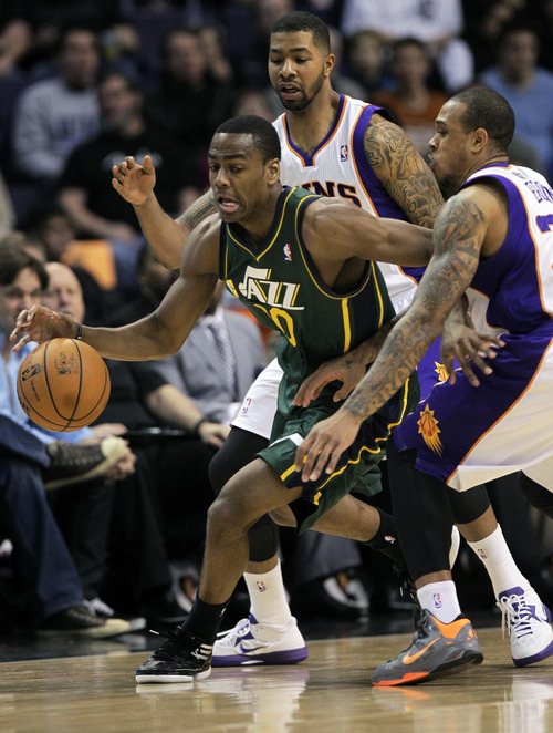 Utah Jazz forward Alec Burks, left, is pressured by Phoenix Suns guard Shannon Brown, right, and Markieff Morris, rear, during the first half of an NBA basketball game, Friday, Jan. 4, 2013, in Phoenix. The Jazz won 87-80. (AP Photo/Matt York)