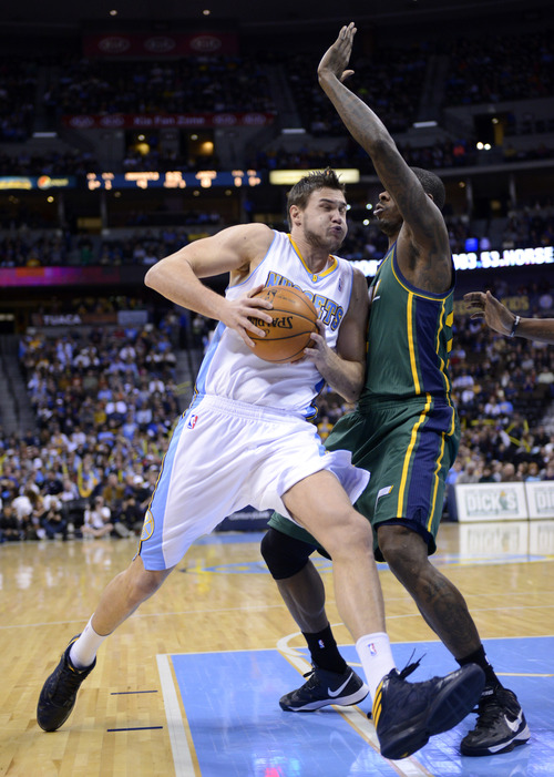 Denver Nuggets forward Danilo Gallinari, left, from Italy, is fouled by Utah Jazz forward Marvin Williams, right, during the first quarter of an NBA basketball game on Saturday, Jan. 5, 2013, in Denver. (AP Photo/Jack Dempsey)