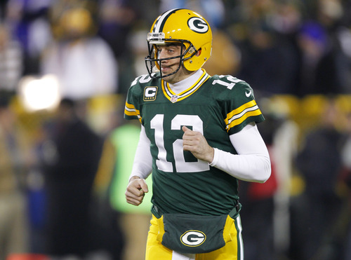 Green Bay Packers quarterback Aaron Rodgers (12) runs on the field as he warms up before an NFL wild card playoff football game against the Minnesota Vikings Saturday, Jan. 5, 2013, in Green Bay, Wis. (AP Photo/Mike Roemer)
