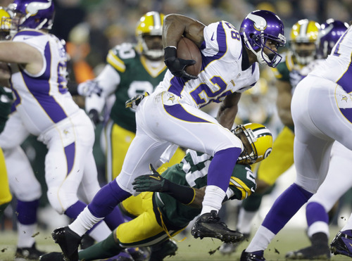 Minnesota Vikings running back Adrian Peterson (28) tries to break a tackily by Green Bay Packers strong safety Charles Woodson (21) during the first half of an NFL wild card playoff football game Saturday, Jan. 5, 2013, in Green Bay, Wis. (AP Photo/Jeffrey Phelps)
