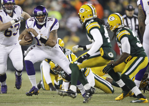 Minnesota Vikings quarterback Joe Webb (14) runs from Green Bay Packers defenders during the first half of an NFL wild card playoff football game Saturday, Jan. 5, 2013, in Green Bay, Wis. (AP Photo/Kiichiro Sato)