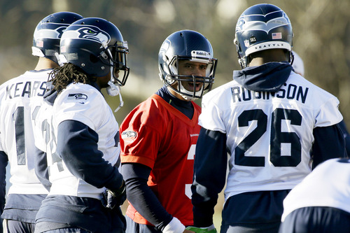 Seattle Seahawks quarterback Russell Wilson, center, talks to teammates including fullback Michael Robinson (26) and wide receiver Jermaine Kearse (11) in the huddle during NFL football practice, Thursday, Jan. 3, 2013, in Renton, Wash. The Seahawks are scheduled to face the Washington Redskins Sunday in an NFC wild card playoff game. (AP Photo/Ted S. Warren)