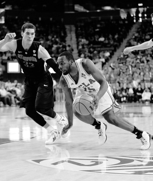 UCLA's Shabazz Muhammad, center, drives past Stanford's Dwight Powell during the second half of an NCAA college basketball game against Stanford in Los Angeles, Saturday, Jan. 5, 2013. UCLA won 68-60. (AP Photo/Jae C. Hong)