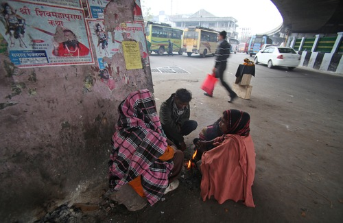 Homeless Indians warm themselves near a fire on a cold and foggy morning in Jammu, India, Saturday, Jan. 5, 2013. More than 100 people have died of exposure as northern India deals with historically cold temperatures. (AP Photo/Channi Anand)