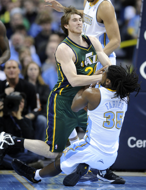Utah Jazz guard Gordon Hayward (20) and Denver Nuggets forward Kenneth Faried (35) fight for a loose ball during the first quarter of an NBA basketball game on Saturday, Jan. 5, 2013, in Denver. (AP Photo/Jack Dempsey)