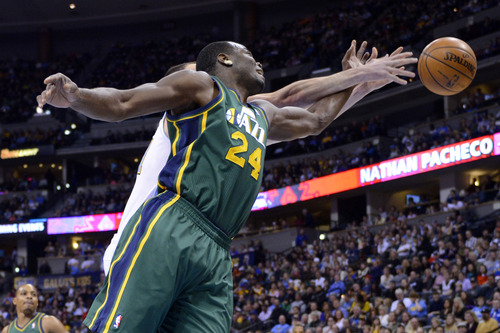 Utah Jazz forward Paul Millsap (24) and Denver Nuggets center Kosta Koufos go after a rebound during the first quarter of an NBA basketball game on Saturday, Jan. 5, 2013, in Denver. (AP Photo/Jack Dempsey)