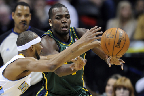 Utah Jazz forward Paul Millsap, right, and Denver Nuggets forward Corey Brewer reach for a loose ball during the second quarter of an NBA basketball game on Saturday, Jan. 5, 2013, in Denver. (AP Photo/Jack Dempsey)
