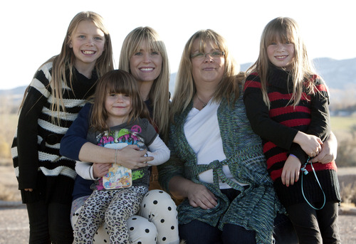 Steve Griffin    The Salt Lake Tribune Lizzie Badger holds her daughter, LuLu, as they pose for a picture with Camie Lacey and her daughters, Abigail and Samie, at Ashley Maynard's grave at the Vernal Cemetery in Vernal, Utah Saturday October 27, 2012. Lacey's daughter, Ashely, 12, died three years ago, darting in front of a car on her way to school. The family donated her organs, and her liver saved LuLu's life. The two families have become friends and met in the small Utah town for the kids to visit a corn maze and visit Ashley's grave.
