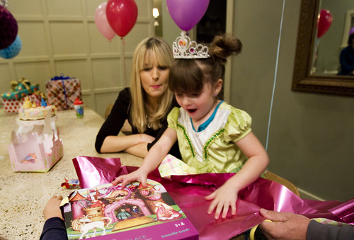 Kim Raff     The Salt Lake Tribune LuLu Badger, who received a liver transplant in 2010, opens presents as her mother, Lizzie Badger, looks on while celebrating her fourth birthday in her home in Salt Lake City on December 8, 2012.