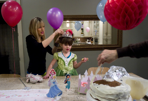 Kim Raff     The Salt Lake Tribune LuLu Badger, who received a liver transplant in 2010, lets her mother Lizzie Badger pin a princess crown in her hair as grandmother Bonnie Barnum ices the cake while celebrating Lulu's fourth birthday at her home in Salt Lake City on December 8, 2012.
